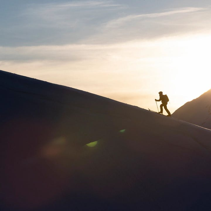 Photograph by Jeff Cricco of man skinning up a mountain at sunrise