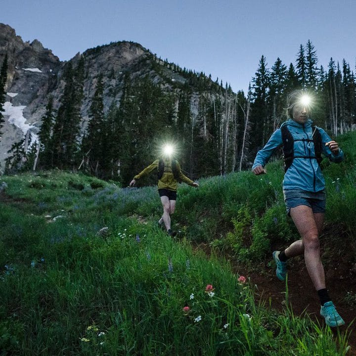 Photograph by Christian Adam of Mary McIntyre and a man running outdoors with headlamps before dawn
