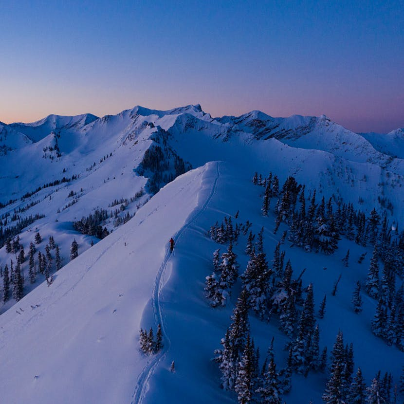 Skier touring along a ridgeline at dawn.