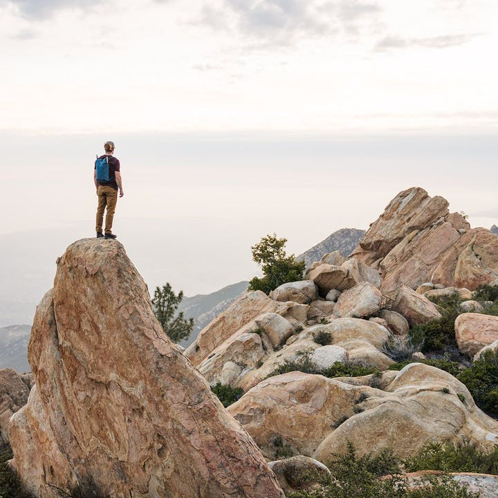 A photo by Christian Adam of a man standing on a boulder overlooking a vista.