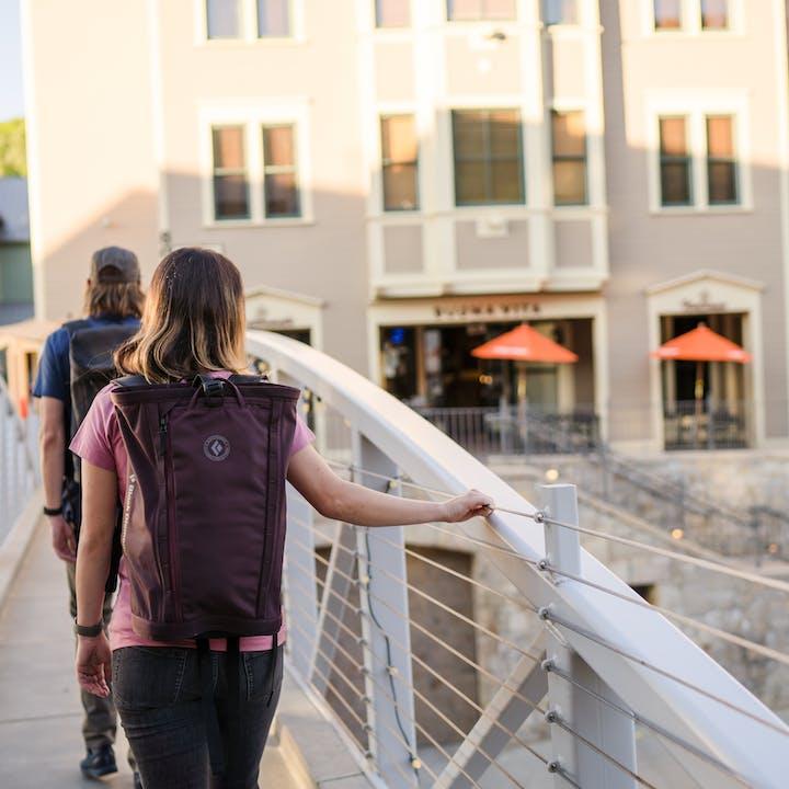 two people walking across a bridge with Black Diamond transit packs | Day Packs