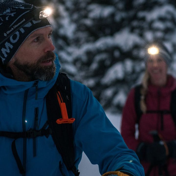 Photograph by Andy Earl of two people using headlamps while skinning up a mountain before dawn