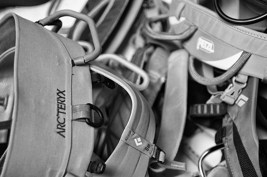 A pile of harnesses from BD, Petzly, and Arc'teryx