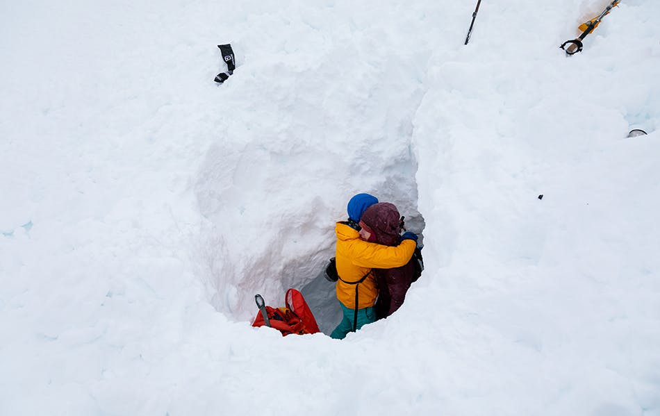 two skiers hugging after they made the rescue from the snow hole