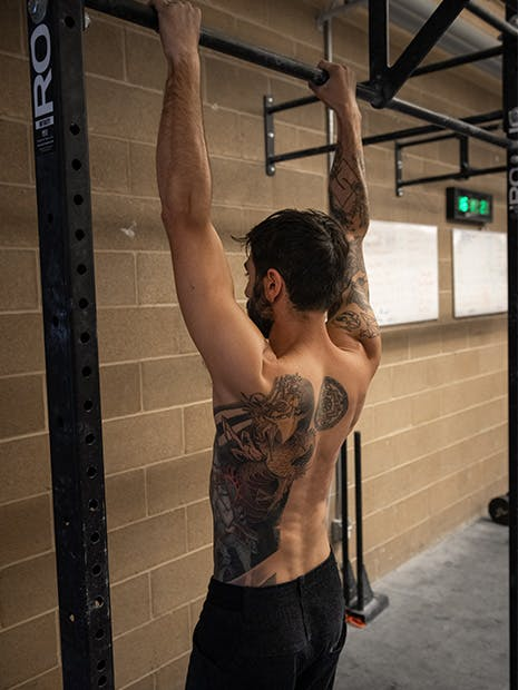 Sam Elias hanging from pull-up bar