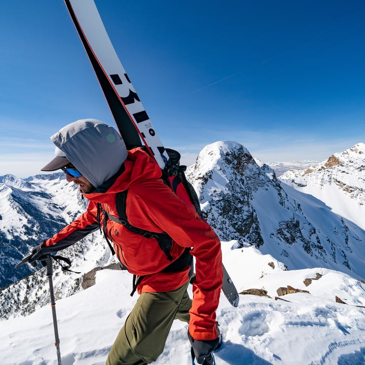 Man climbing up steep mountain with skis