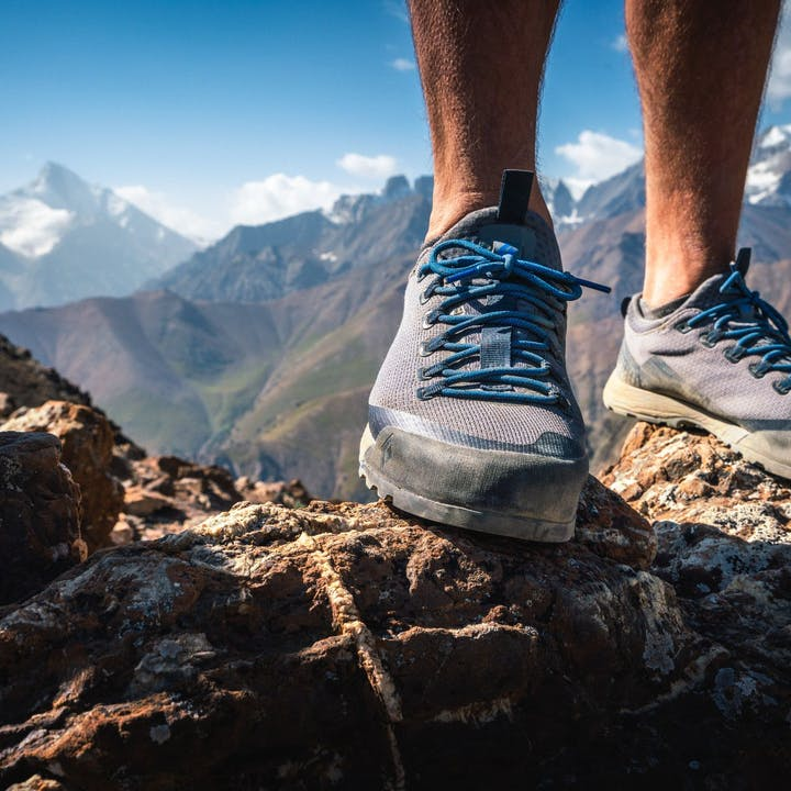 Photograph by Eric Bissell featuring a man's feet in approach shoes on top of a mountain ridge