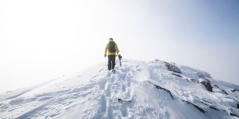 Snowboarder on ridge carrying board