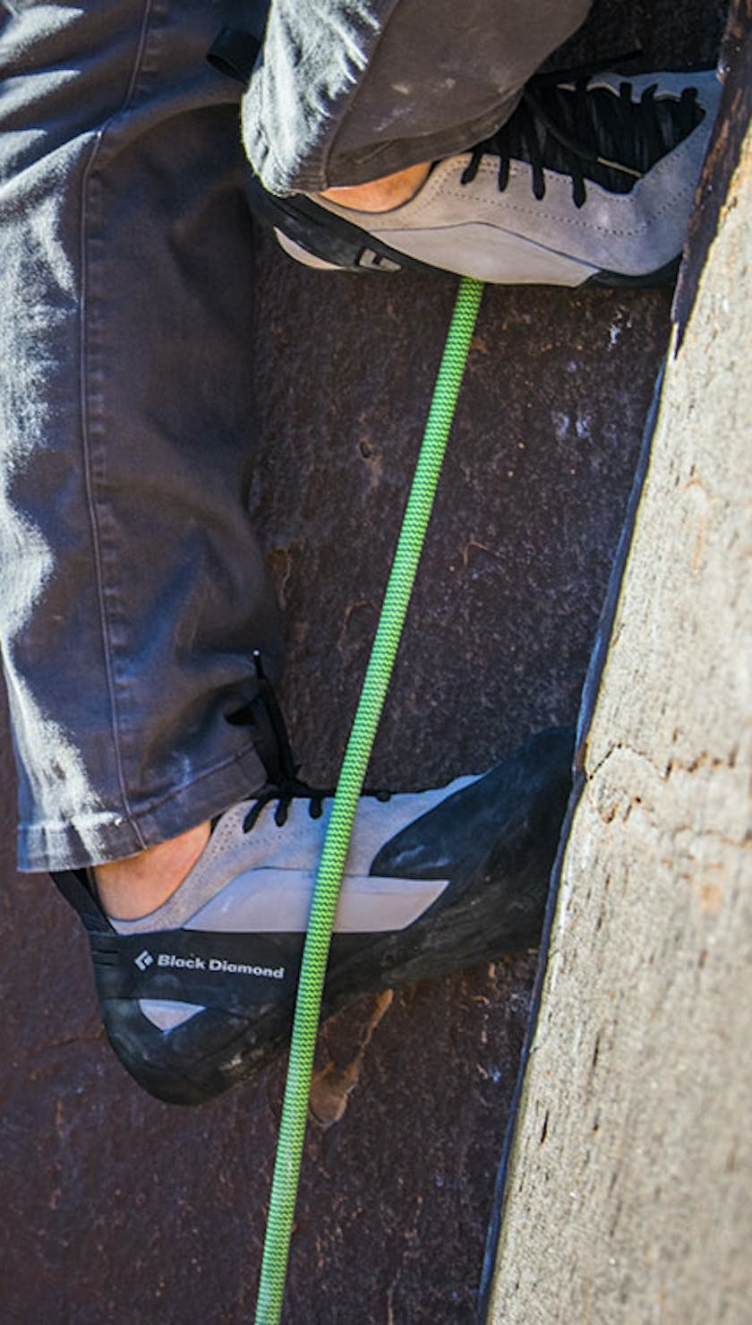 man working up a crack in Black Diamond climbing shoes