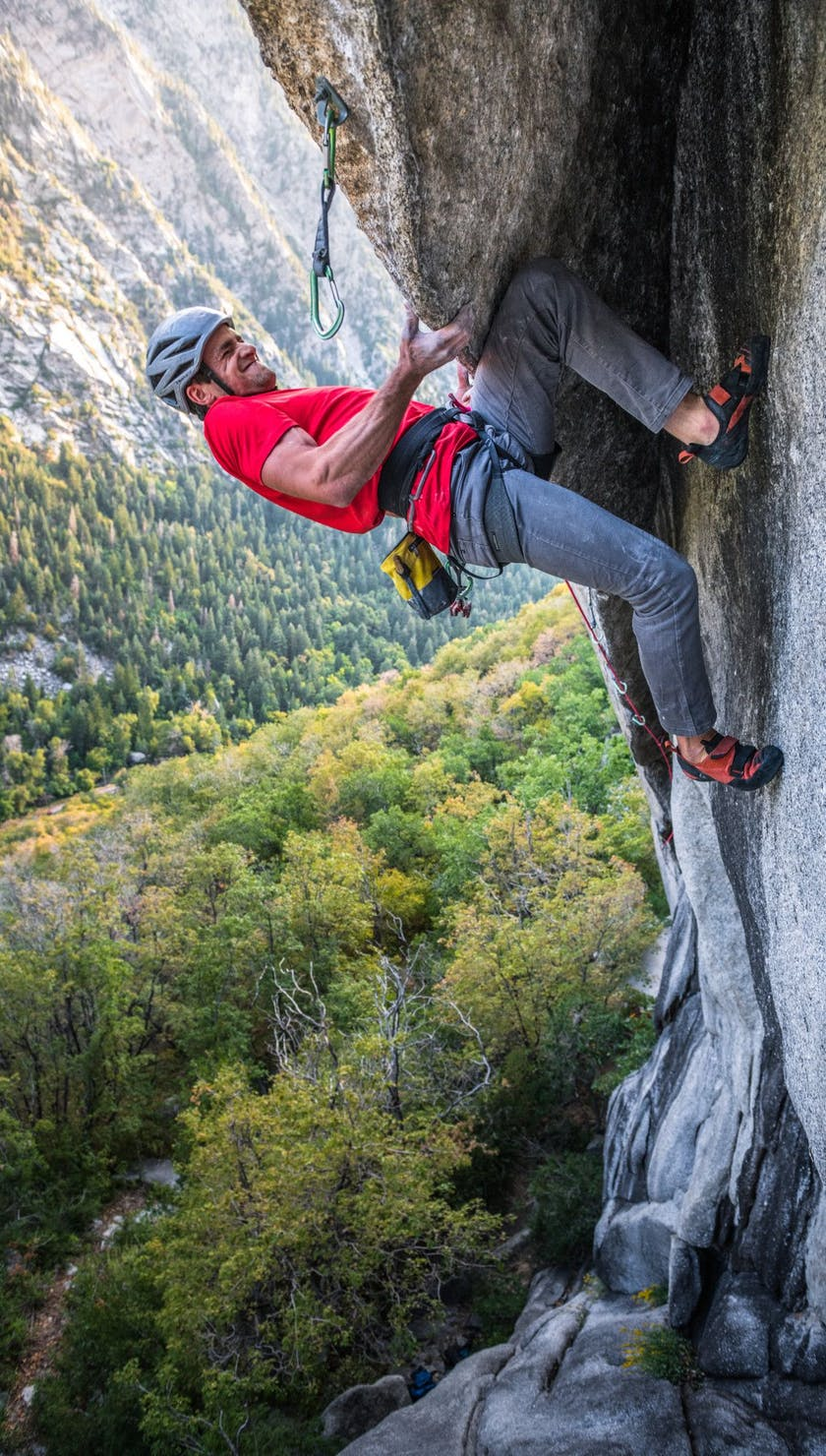Man rock climbing with solution guide harness