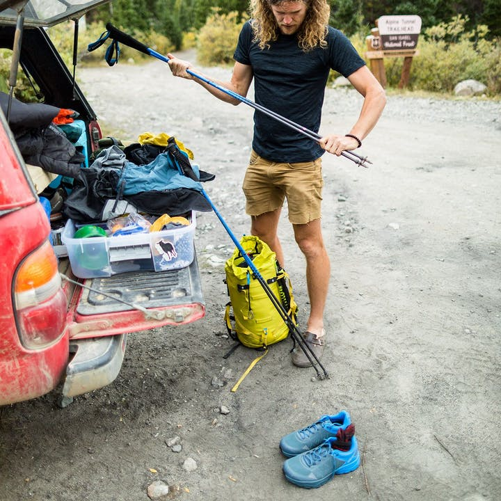Photograph by Forest Woodward of Joe Grant preparing trekking poles outside