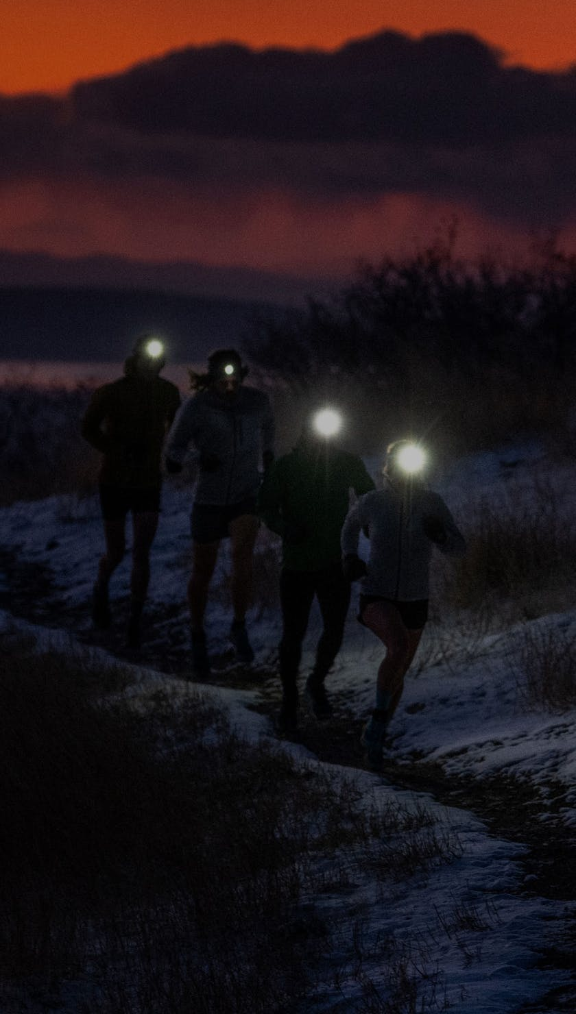 runners going up a trail in the dark with rechargeable headlamps