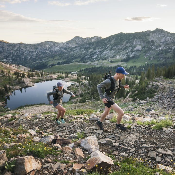 A man and Mary McIntyre trail running in the mountains