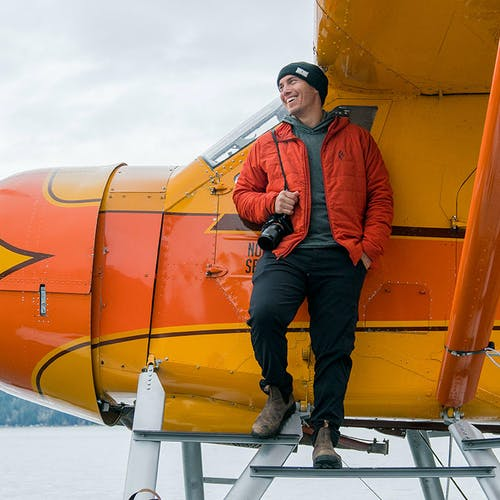 Chris Burkard standing on steps of plane