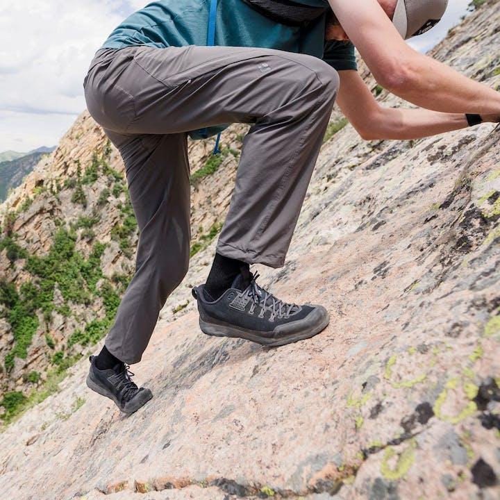 Photograph by Christian Adam of a man scrambling up a mountain face