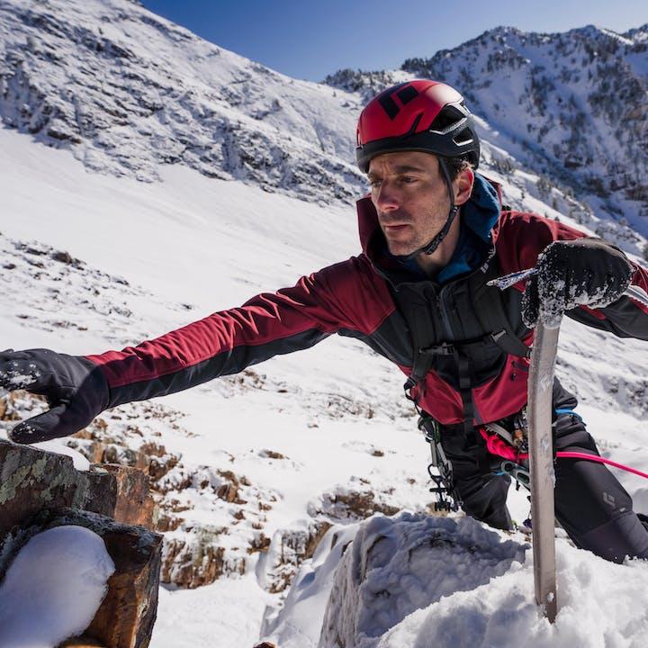 Man climbing up snowy mountain in red fleece jacket