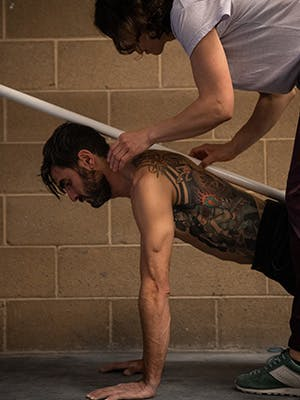 Photo of Esther Smith holding a pole on Sam Elias' back while he holds upper plank formation.