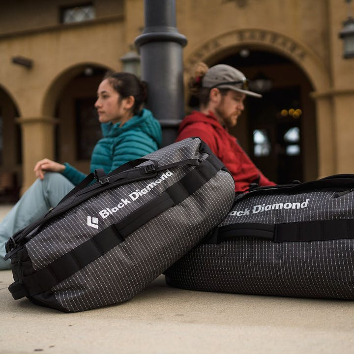 Photograph by Christian Adam of two people waiting for a train with their BD duffels