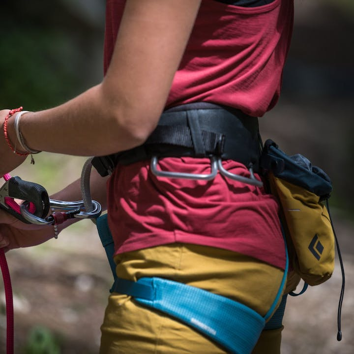 Photograph by Andy Earl of woman belaying outdoors