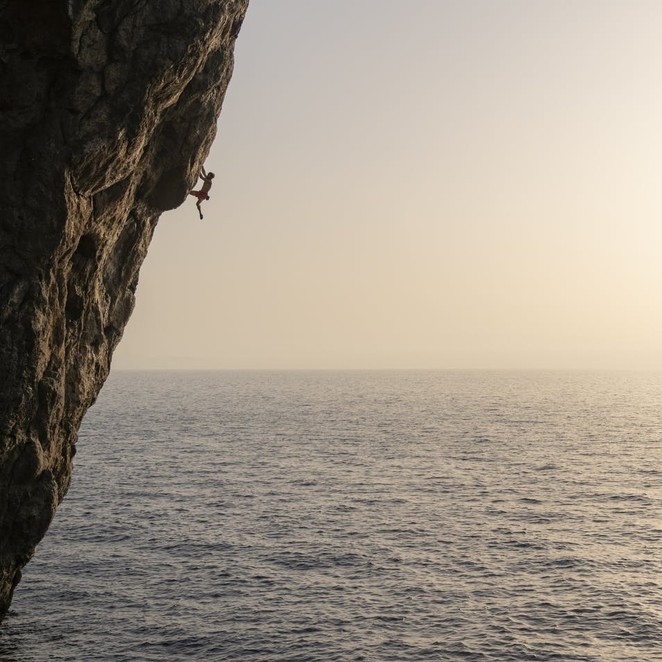 Climber climbing, ocean in background