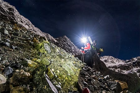 Photo of Antte Lauhamaa hiking up a mountain with a headlamp on.
