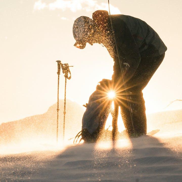 Isaac Freeland getting into his ski pack | Black Diamond ski backpack