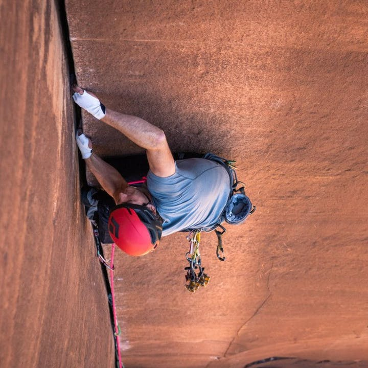 Photograph by Andy Earl of a man crack climbing in the desert