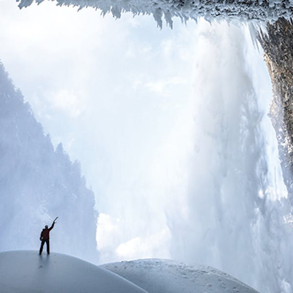 Climber surrounded by snowy landscape.