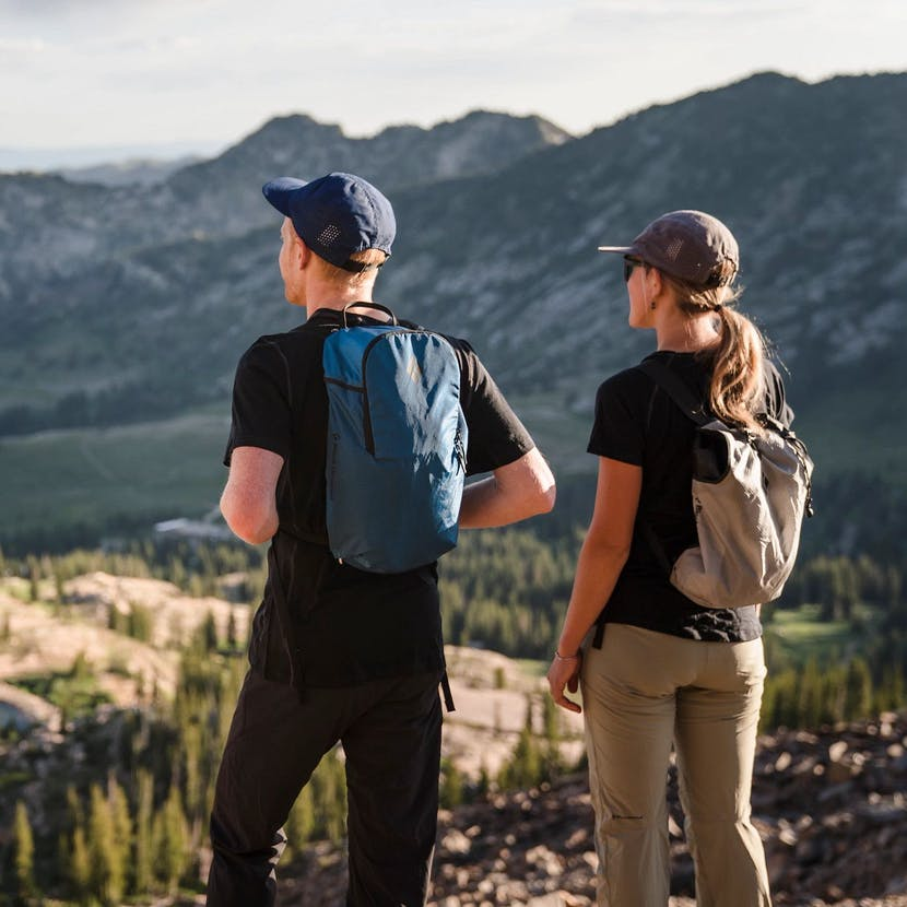 Two Hikers in the Wasatch Mountains overlooking a lake.