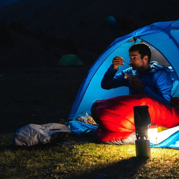Photograph by Eric Bissell of man eating in tent by lantern light