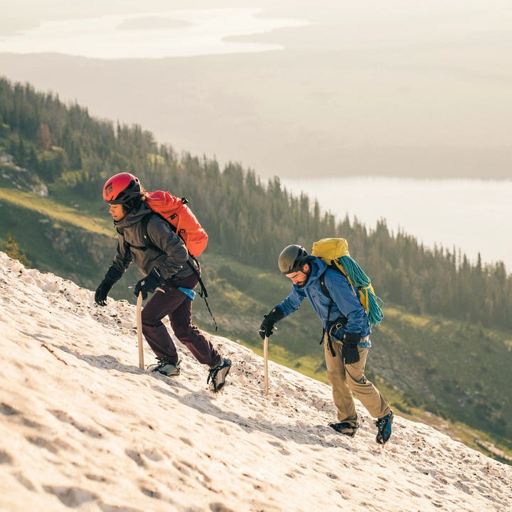Photograph by Christian Adam of woman and man trekking up snowy terrain