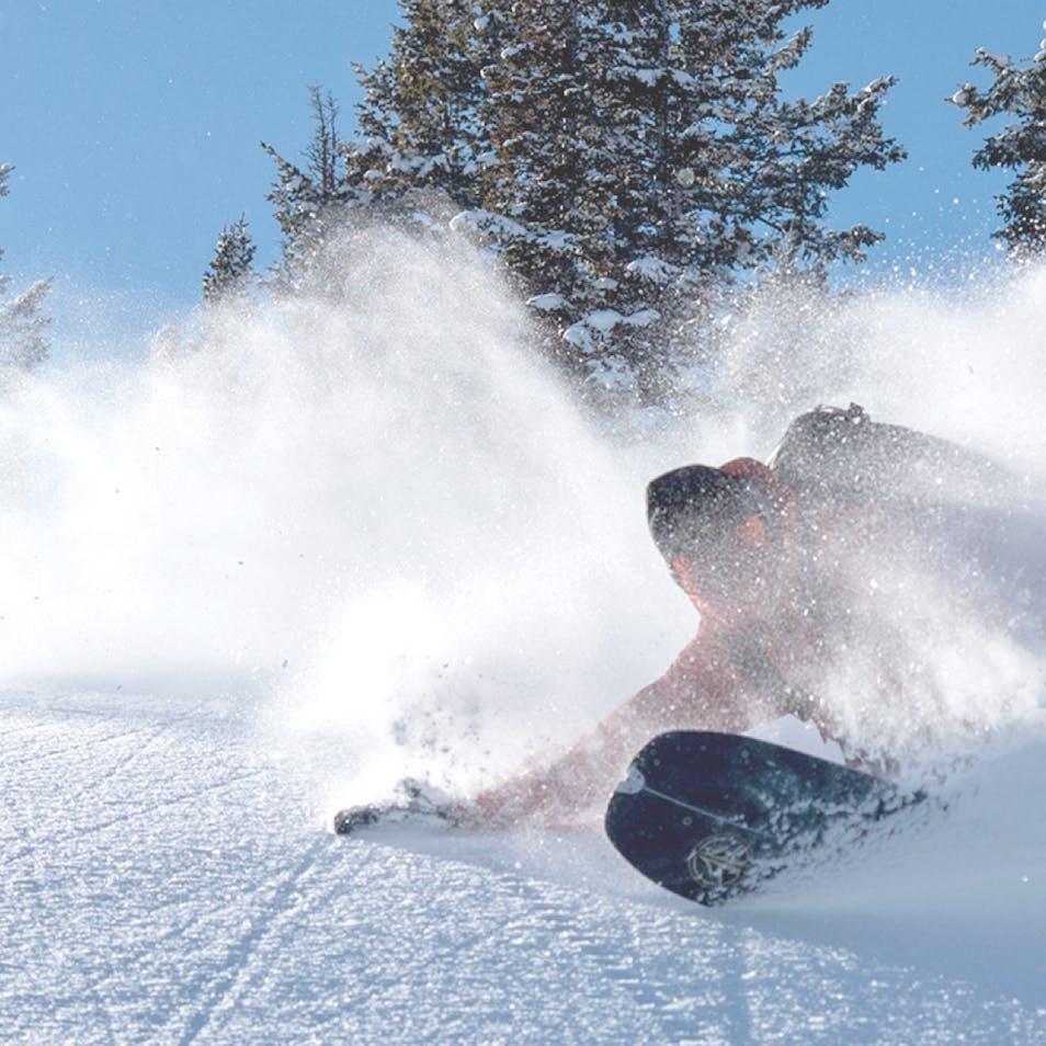 BD Athlete Bjorn Leines carving his snowboard through powder