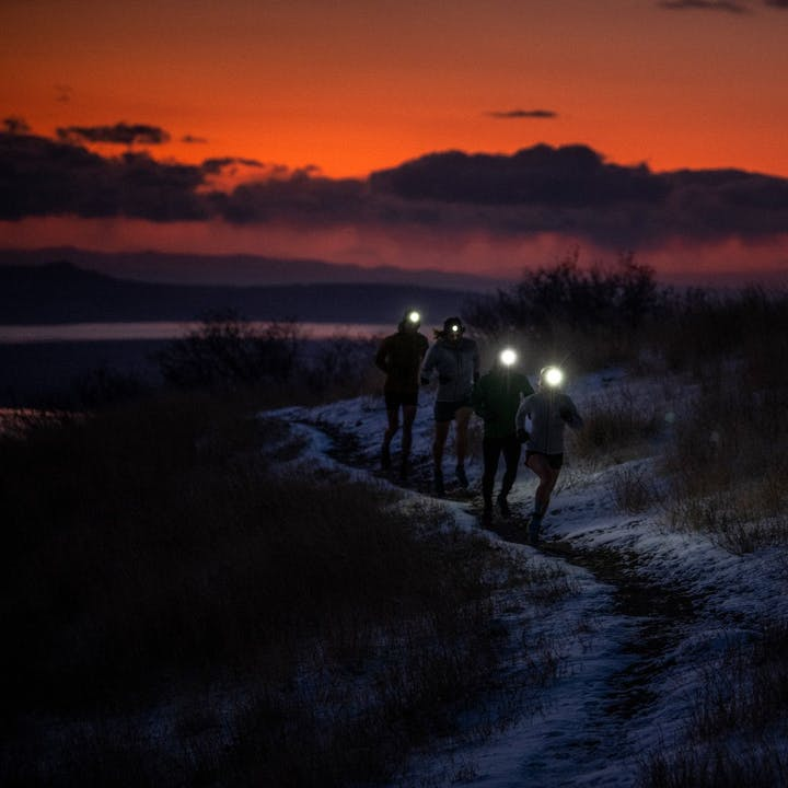 Photograph by Alex Mlynarek of a group of runners using headlamps before sunrise