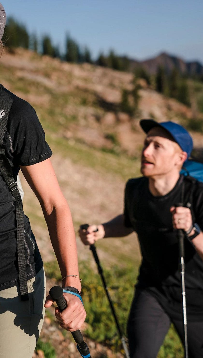 Mary McIntyre wearing a W Flux Merino shirt while hiking with a man outside