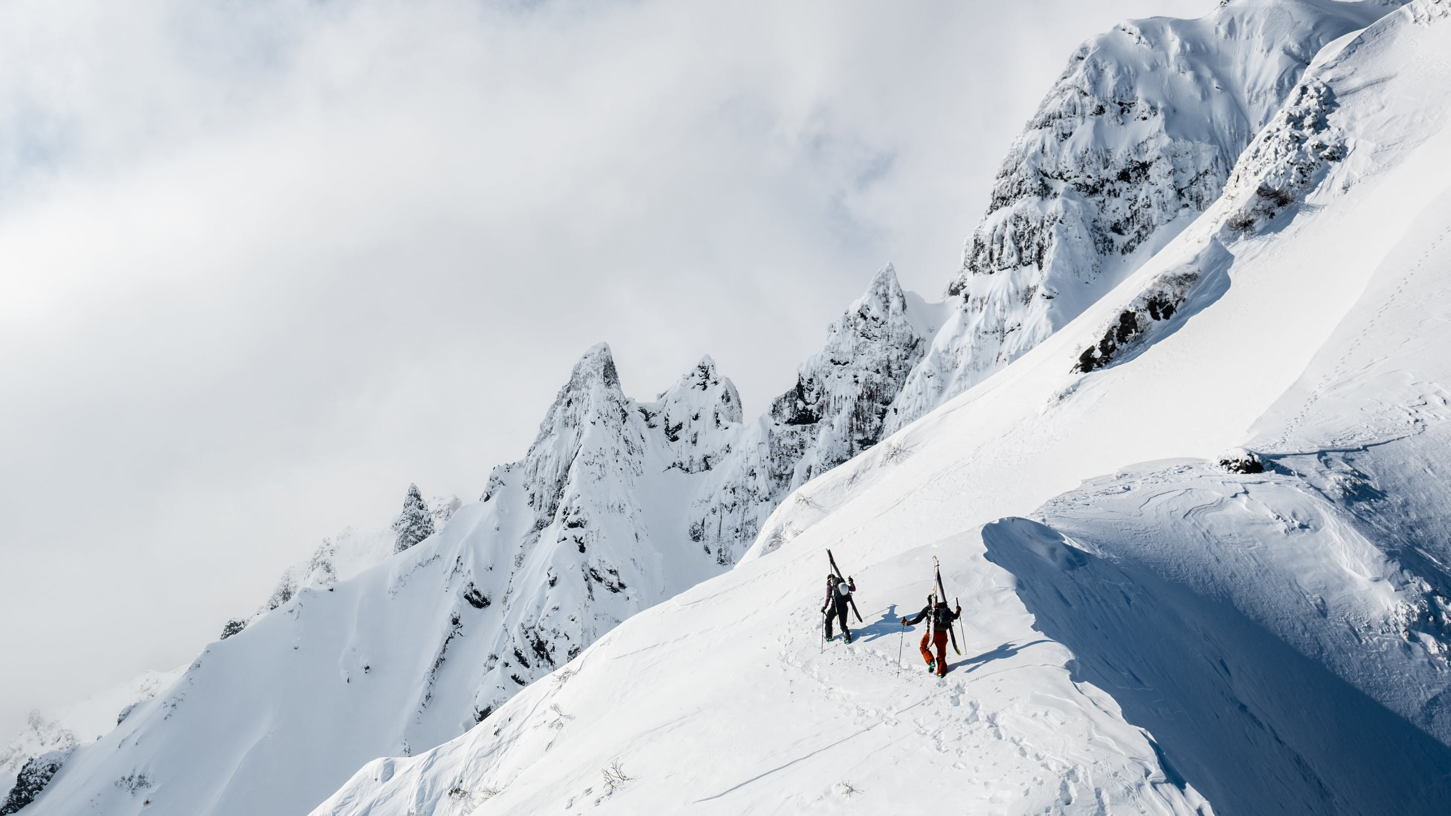 two skiers working along a ridgeline