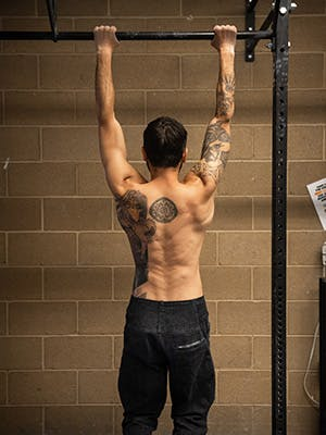 Photo of Sam Elias hanging from a pull up bar.