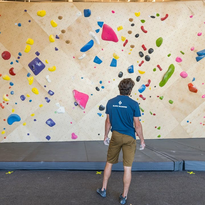 Photograph by Christian Adam of a man preparing to boulder in a gym