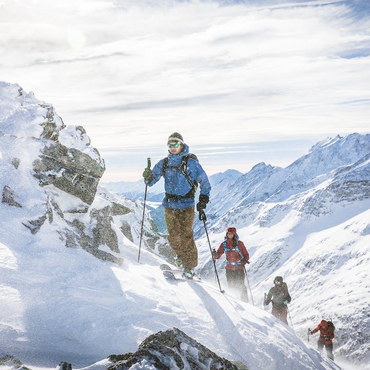 skiers hiking up a ridge