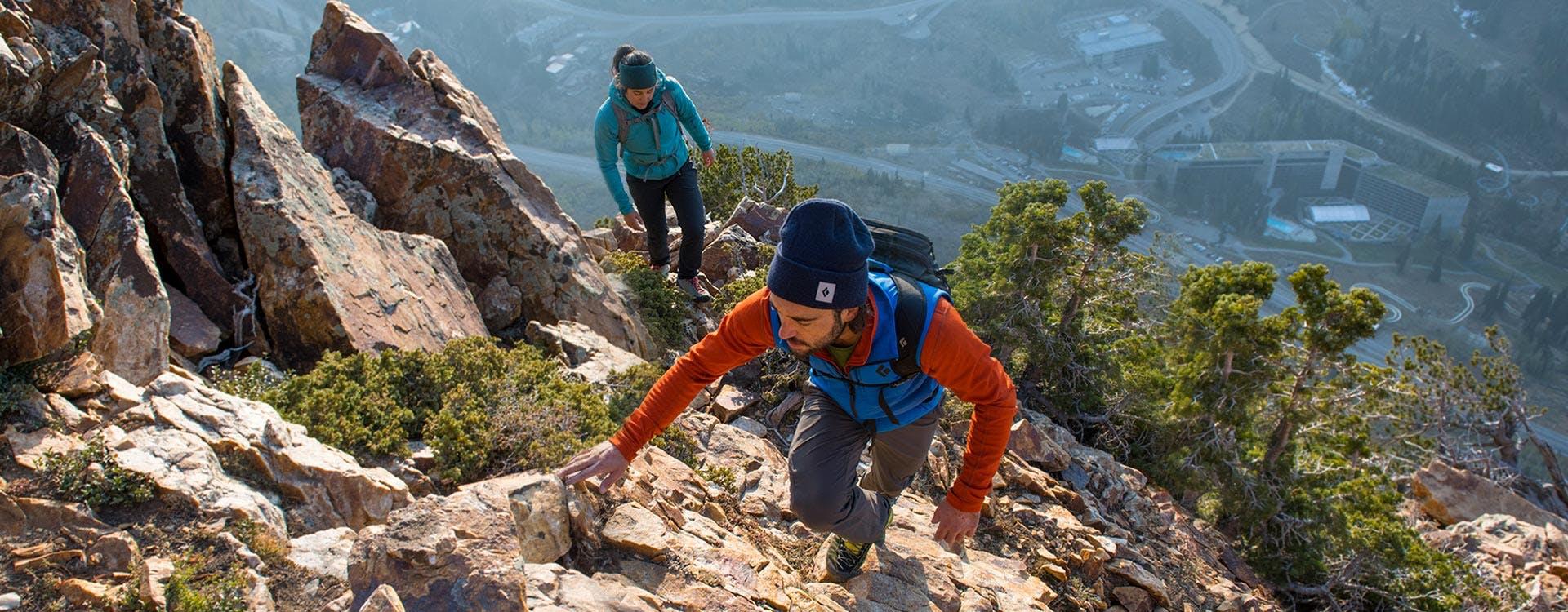 man and woman climbing a ridge