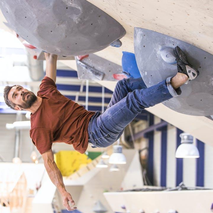 man climbing indoors in black diamond climbing pants