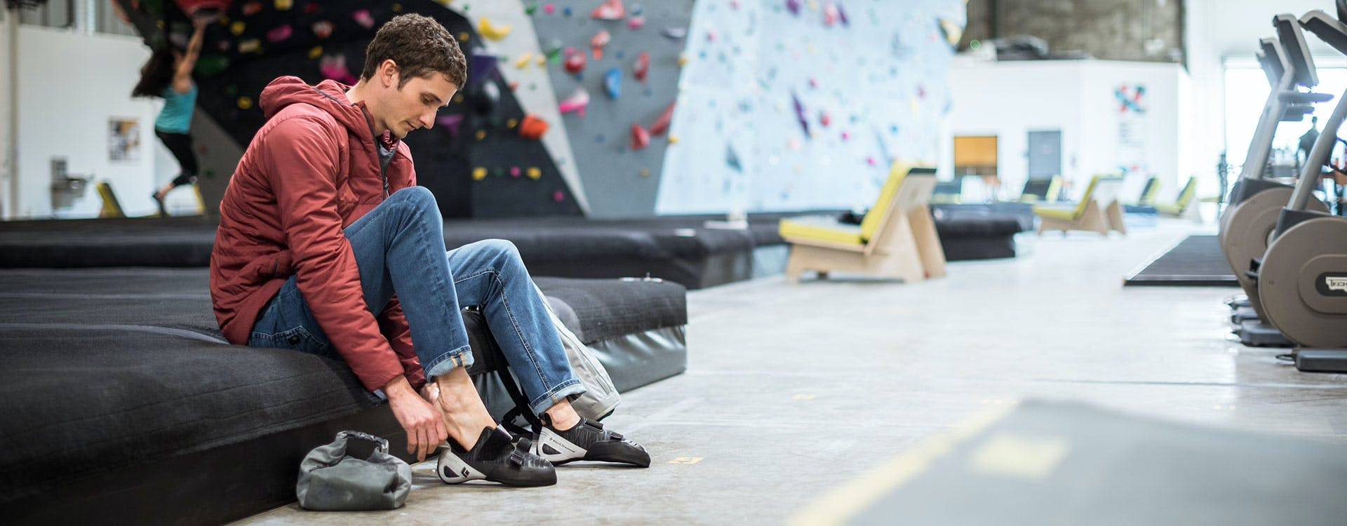 man putting on climbing shoes