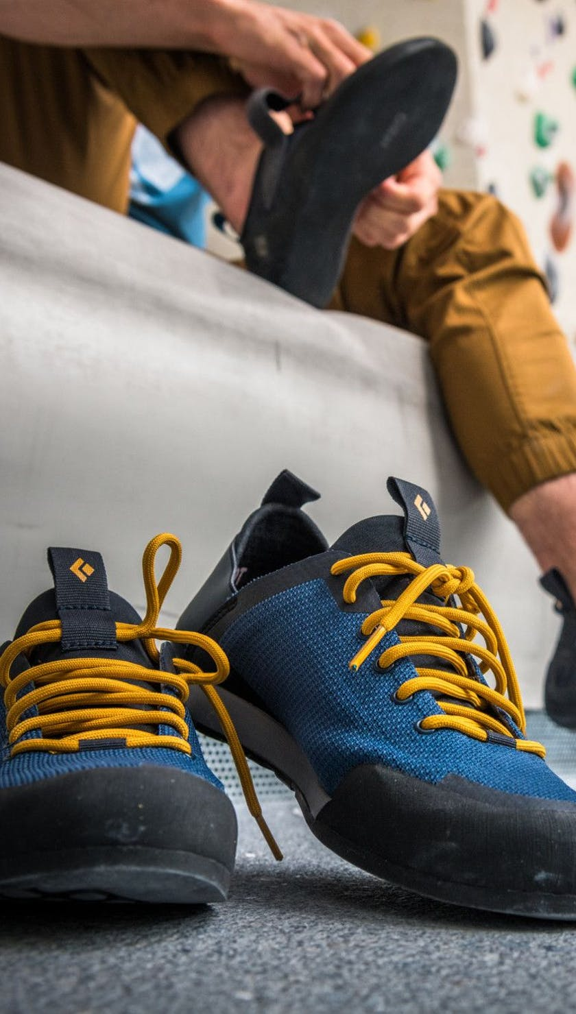 A pair of session shoes on the ground while two people put on climbing shoes in the background