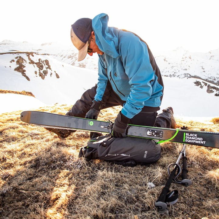 Photograph by Jeff Cricco of man removing skis from pack outdoors