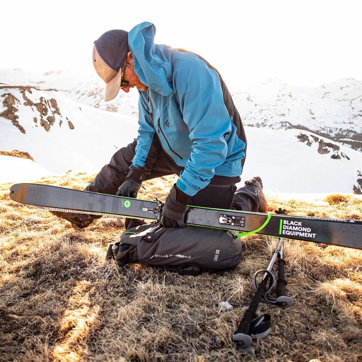 man putting skis on pack