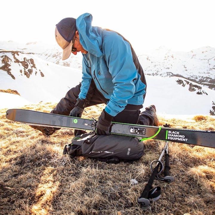 man putting skis on pack
