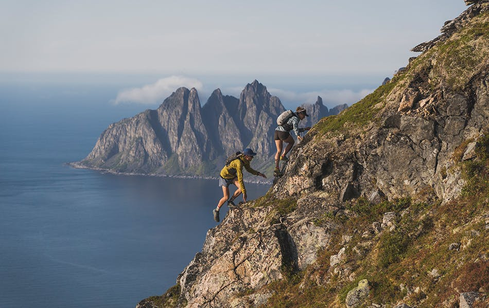 Hillary Gerardi and Kyle Richardson scramble up a mountain face in Norway