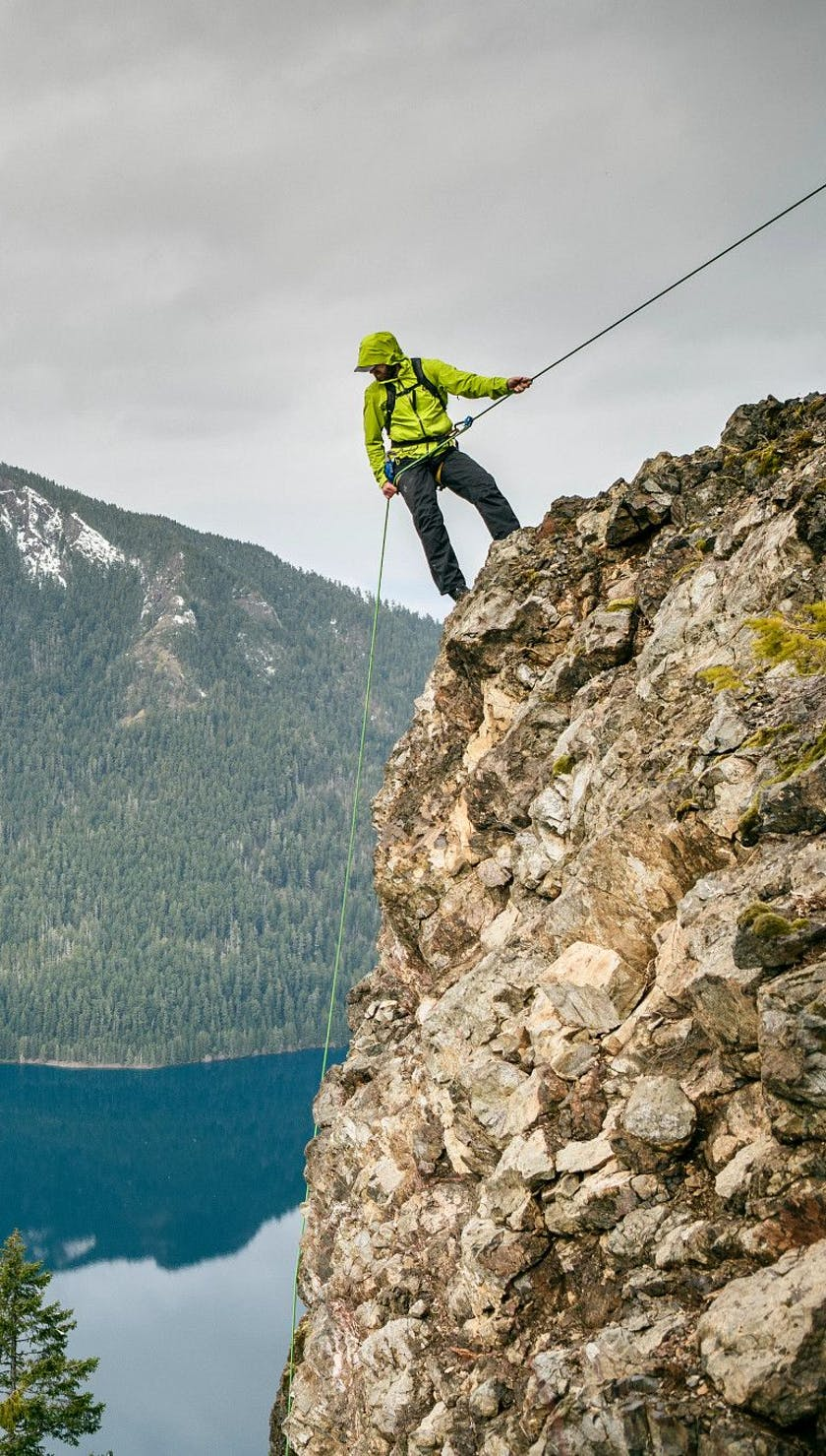 A man repelling while wearing the Stormline Stretch Rain Shell