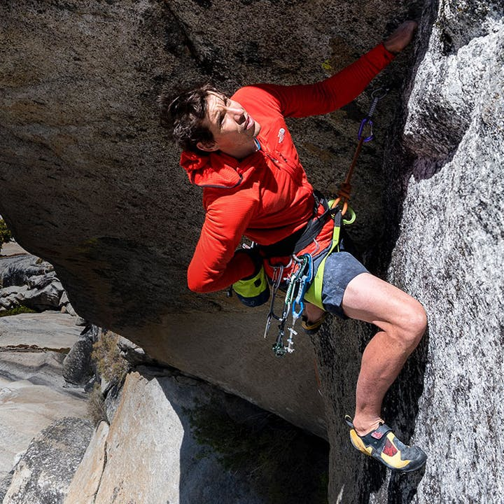 Alex Honnold reaching to place a piece of rock protection