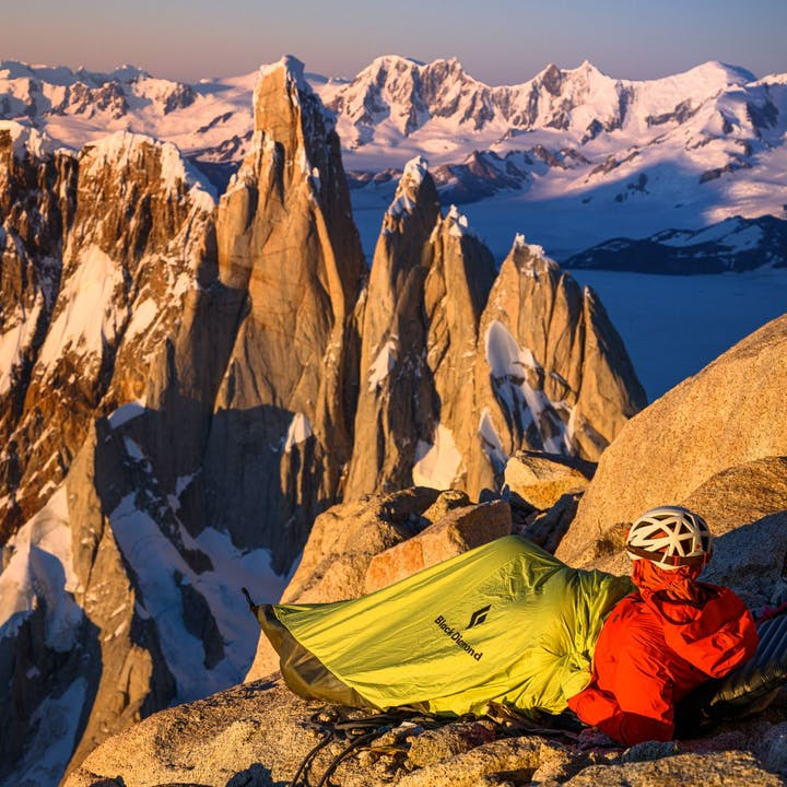 Photograph by Ted Hesser of man in bivvy overlooking the mountains