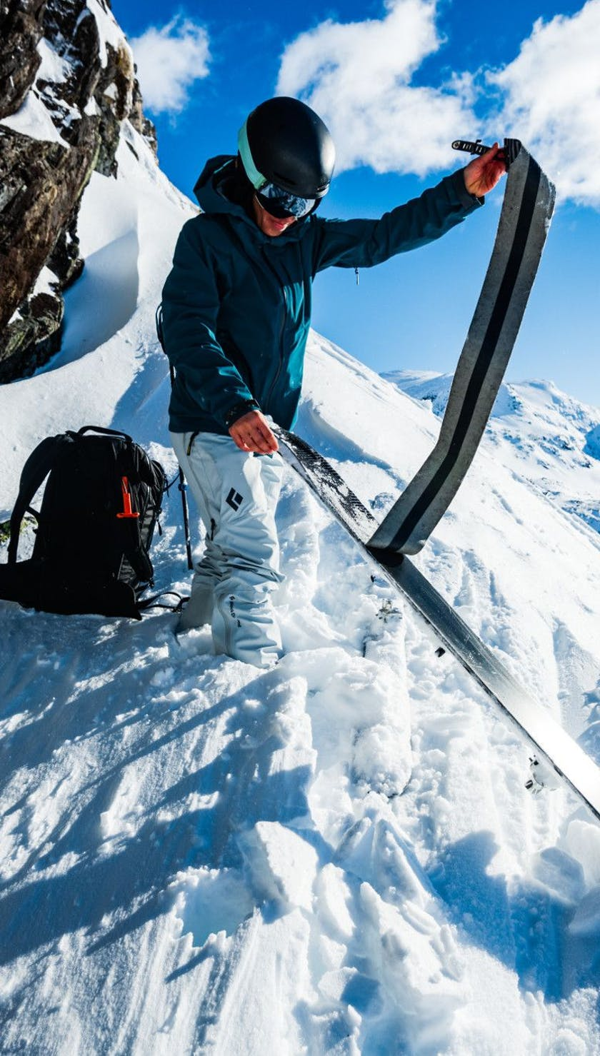 A person pulling Glidelite Skin off of their skis on a snowy mountain